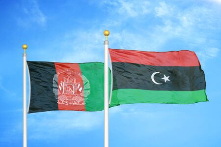 Afghanistan and Libya  two flags on flagpoles and blue cloudy sky background