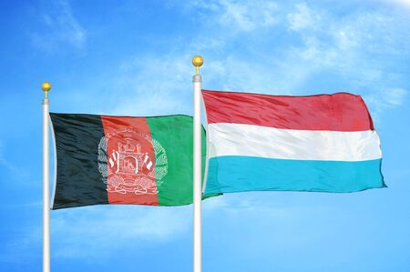 Afghanistan and Luxembourg  two flags on flagpoles and blue cloudy sky background