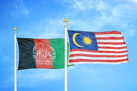 Afghanistan and Malaysia  two flags on flagpoles and blue cloudy sky background