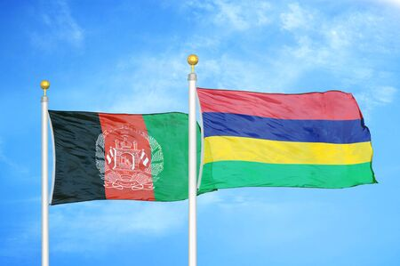 Afghanistan and Mauritius  two flags on flagpoles and blue cloudy sky background