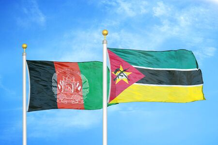 Afghanistan and Mozambique  two flags on flagpoles and blue cloudy sky background