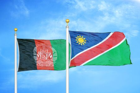 Afghanistan and Namibia  two flags on flagpoles and blue cloudy sky background