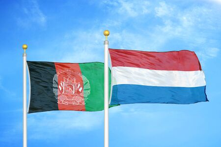 Afghanistan and Netherlands  two flags on flagpoles and blue cloudy sky background