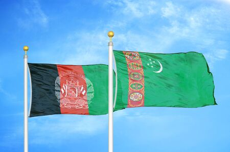 Afghanistan and Turkmenistan  two flags on flagpoles and blue cloudy sky background