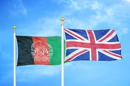 Afghanistan and United Kingdom  two flags on flagpoles and blue cloudy sky background