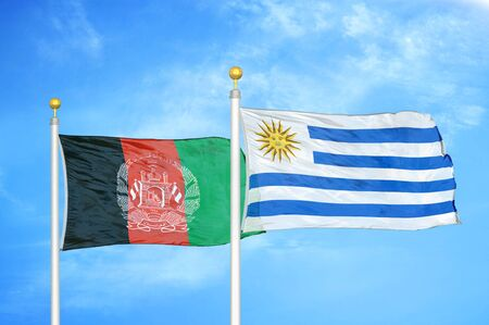 Afghanistan and Uruguay  two flags on flagpoles and blue cloudy sky background 版權商用圖片