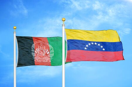 Afghanistan and Venezuela  two flags on flagpoles and blue cloudy sky background