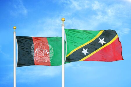 Afghanistan and Saint Kitts and Nevis  two flags on flagpoles and blue cloudy sky background 版權商用圖片
