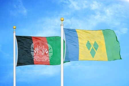 Afghanistan and Saint Vincent and the Grenadines  two flags on flagpoles and blue cloudy sky background