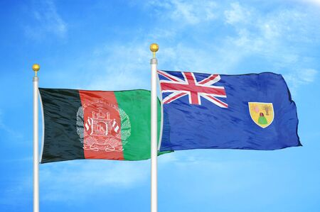 Afghanistan and Turks and Caicos Islands  two flags on flagpoles and blue cloudy sky background