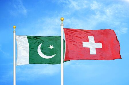 Pakistan and Switzerland two flags on flagpoles and blue cloudy sky background