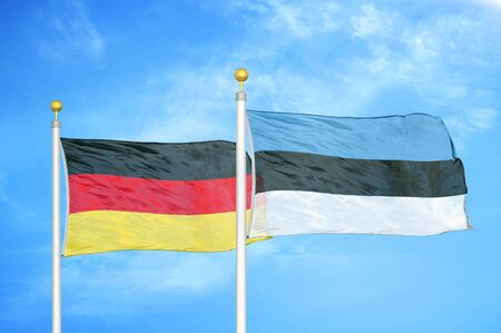 Germany and Estonia two flags on flagpoles and blue cloudy sky background