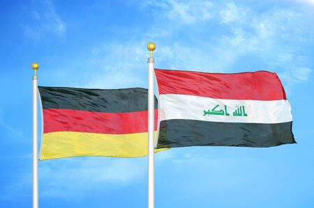 Germany and Iraq two flags on flagpoles and blue cloudy sky background