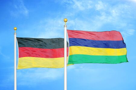 Germany and Mauritius two flags on flagpoles and blue cloudy sky background