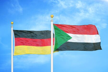 Germany and Sudan two flags on flagpoles and blue cloudy sky background