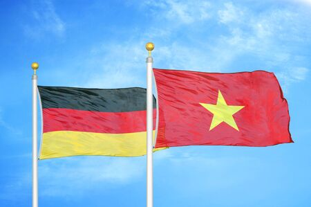 Germany and Vietnam two flags on flagpoles and blue cloudy sky background Stock Photo