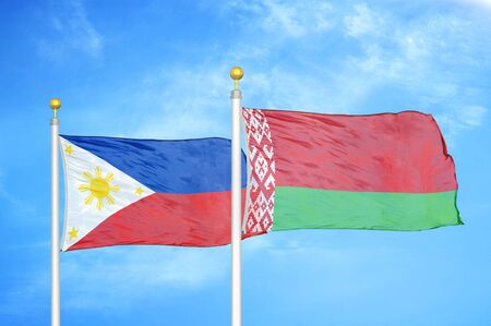 Philippines and Belarus two flags on flagpoles and blue cloudy sky background