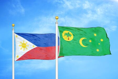 Philippines and Cocos Keeling Islands two flags on flagpoles and blue cloudy sky background