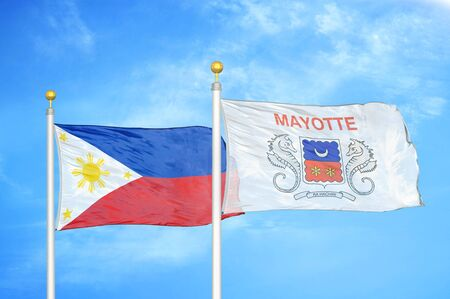 Philippines and Mayotte two flags on flagpoles and blue cloudy sky background