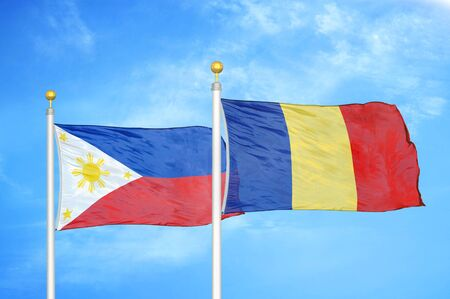 Philippines and Romania two flags on flagpoles and blue cloudy sky background