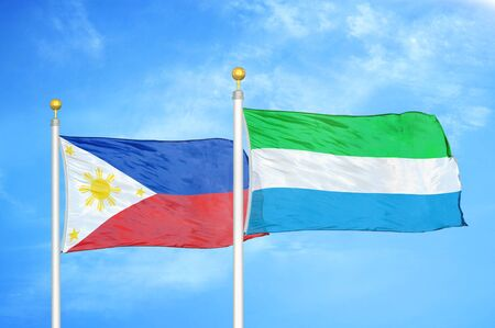 Philippines and Sierra Leone two flags on flagpoles and blue cloudy sky background 版權商用圖片