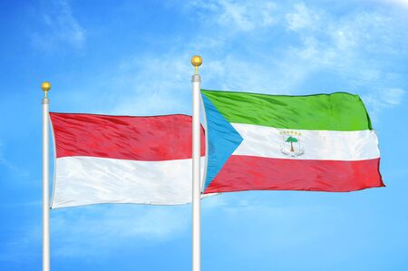 Indonesia and Equatorial Guinea two flags on flagpoles and blue cloudy sky background Stockfoto