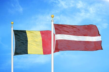 Belgium and Latvia two flags on flagpoles and blue cloudy sky background