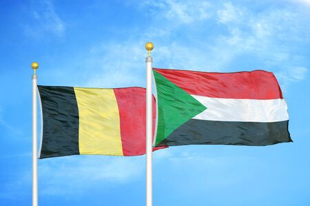 Belgium and Sudan two flags on flagpoles and blue cloudy sky background