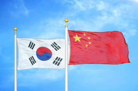 South Korea and China two flags on flagpoles and blue cloudy sky background
