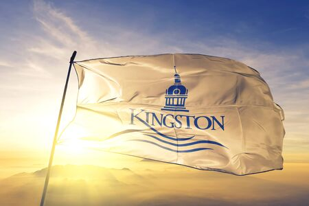 Kingston of Ontario of Canada flag textile cloth fabric waving on the top sunrise mist fog