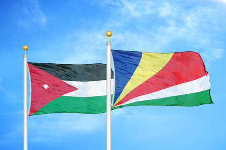 Jordan and Seychelles two flags on flagpoles and blue cloudy sky background