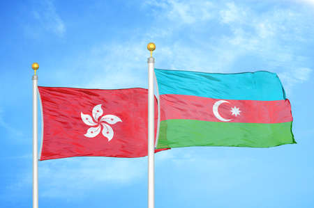 Hong Kong and Azerbaijan two flags on flagpoles and blue cloudy sky background