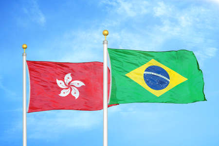 Hong Kong and Brazil two flags on flagpoles and blue cloudy sky background