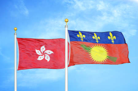 Hong Kong and Guadeloupe two flags on flagpoles and blue cloudy sky background