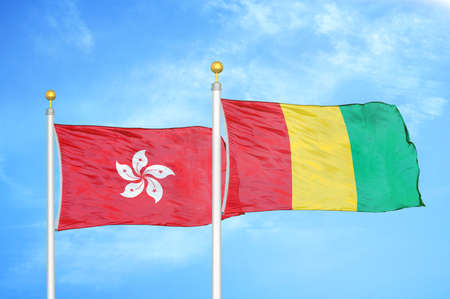 Hong Kong and Guinea two flags on flagpoles and blue cloudy sky background