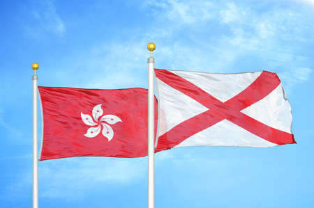 Hong Kong and Northern Ireland two flags on flagpoles and blue cloudy sky background