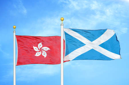 Hong Kong and Scotland two flags on flagpoles and blue cloudy sky background