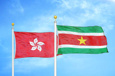 Hong Kong and Suriname two flags on flagpoles and blue cloudy sky background