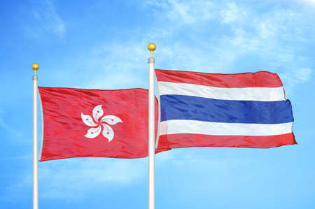 Hong Kong and Thailand two flags on flagpoles and blue cloudy sky background