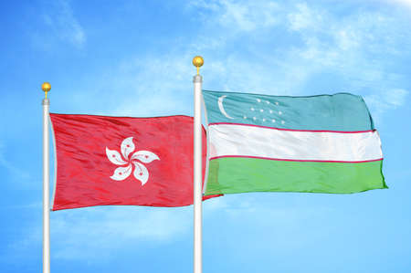 Hong Kong and Uzbekistan two flags on flagpoles and blue cloudy sky background