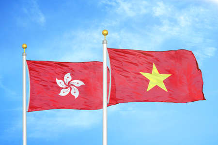 Hong Kong and Vietnam two flags on flagpoles and blue cloudy sky background