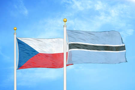 Czech and Botswana two flags on flagpoles and blue cloudy sky background