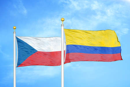Czech and Colombia two flags on flagpoles and blue cloudy sky background