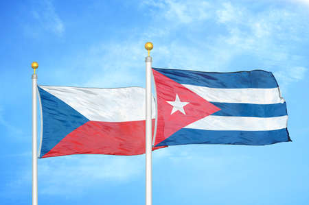 Czech and Cuba two flags on flagpoles and blue cloudy sky background