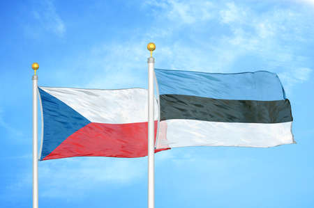 Czech and Estonia two flags on flagpoles and blue cloudy sky background
