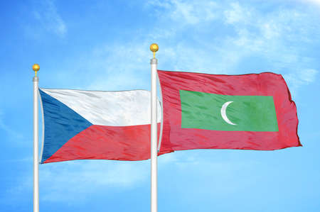Czech and Maldives two flags on flagpoles and blue cloudy sky background