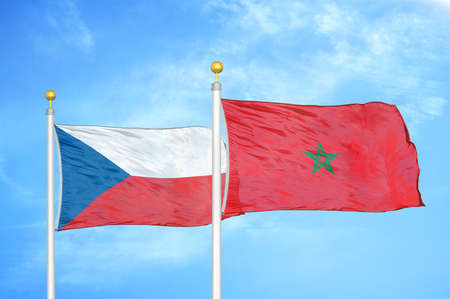 Czech and Morocco two flags on flagpoles and blue cloudy sky background