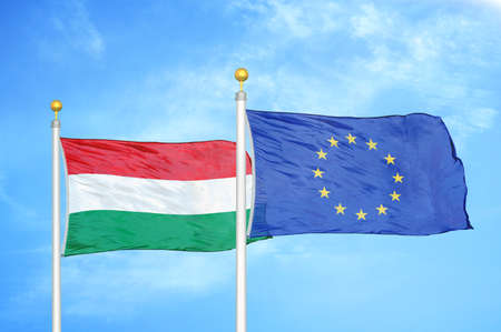 Hungary and European Union two flags on flagpoles and blue cloudy sky background