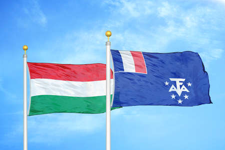 Hungary and French Southern and Antarctic Lands two flags on flagpoles and blue cloudy sky background