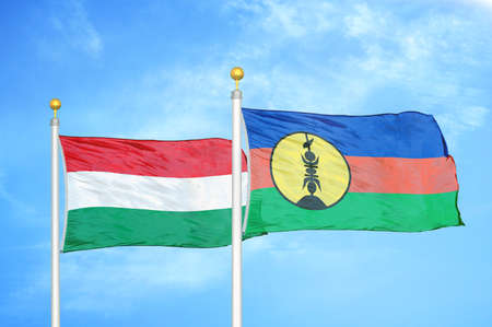 Hungary and New Caledonia two flags on flagpoles and blue cloudy sky background